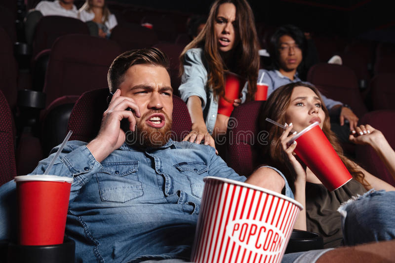 Rude young man talking on mobile phone. Rude young men talking on mobile phone while watching movie at the cinema and disturbing audience royalty free stock images