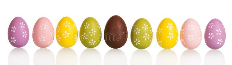 Rudern Sie bunte Ostereier in der Mittelschokolade, lokalisiert auf Weiß stockfoto