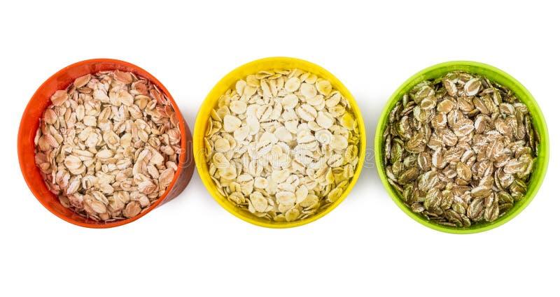 Rudern Sie verschiedene Farben der Schalen mit Hafer, Roggen, Gerstenflocken lizenzfreies stockfoto
