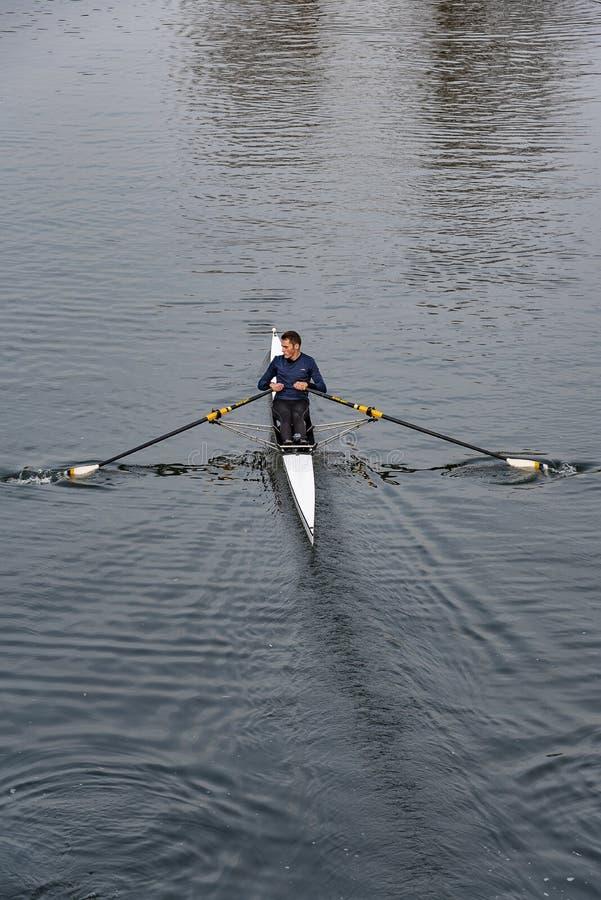 Rudersport des jungen Mannes im einzelnen Boot auf einem Fluss stockbilder