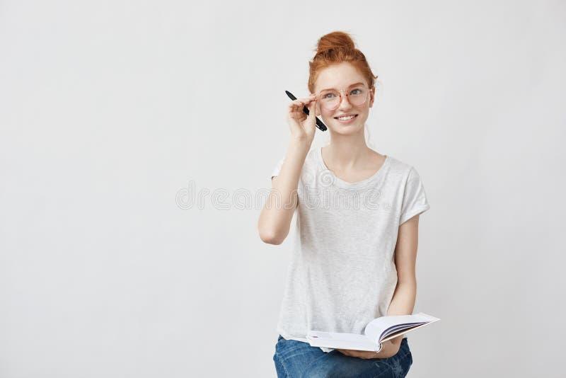 Rudzielec żeński uczeń ono uśmiecha się korygujący szkła trzyma notatnika obrazy royalty free