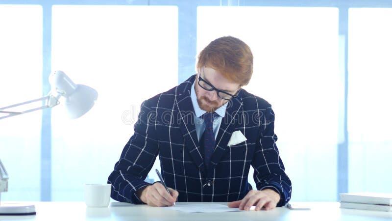 Rudzielec biznesmena papierkowa robota, Writing i działanie na laptopie, obrazy royalty free