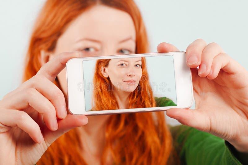 Rudzielec dziewczyna robi selfie używać telefon obraz royalty free