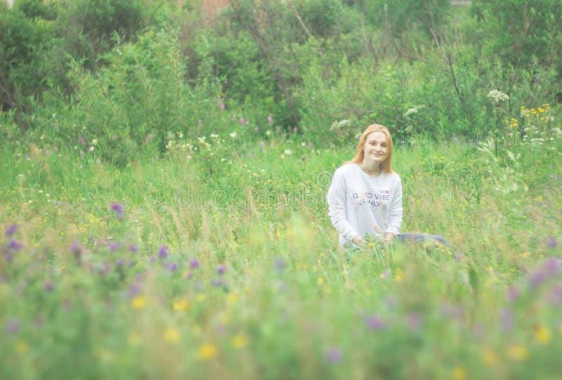 Rudzielec dziewczyny obsiadanie na kwiat łące obrazy royalty free