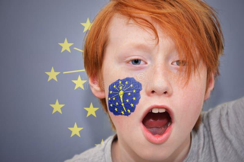 Rudzielec fan chłopiec z Indiana stanu flaga malował na jego twarzy obraz stock