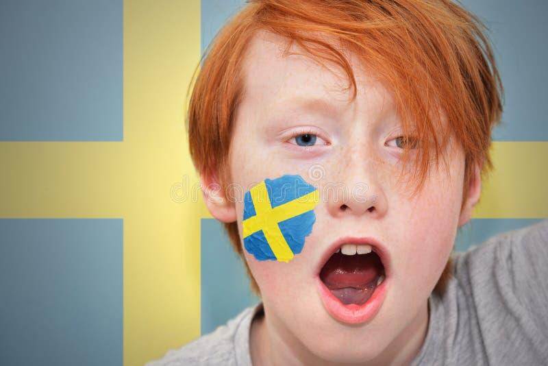 Rudzielec fan chłopiec z szwedzi flaga malował na jego twarzy fotografia royalty free