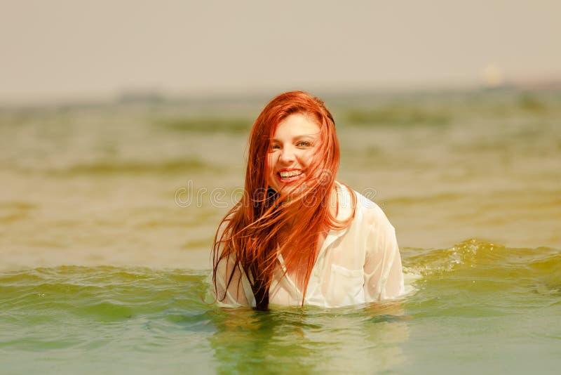 Rudzielec kobieta bawić się w wodzie podczas lata obraz stock