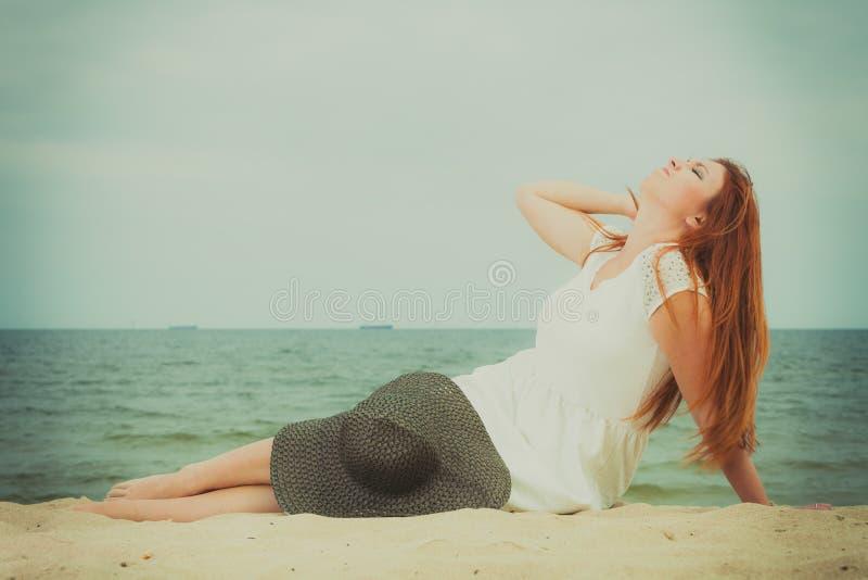 Rudzielec kobieta jest ubranym słońca kapeluszowego lying on the beach na plaży obraz royalty free