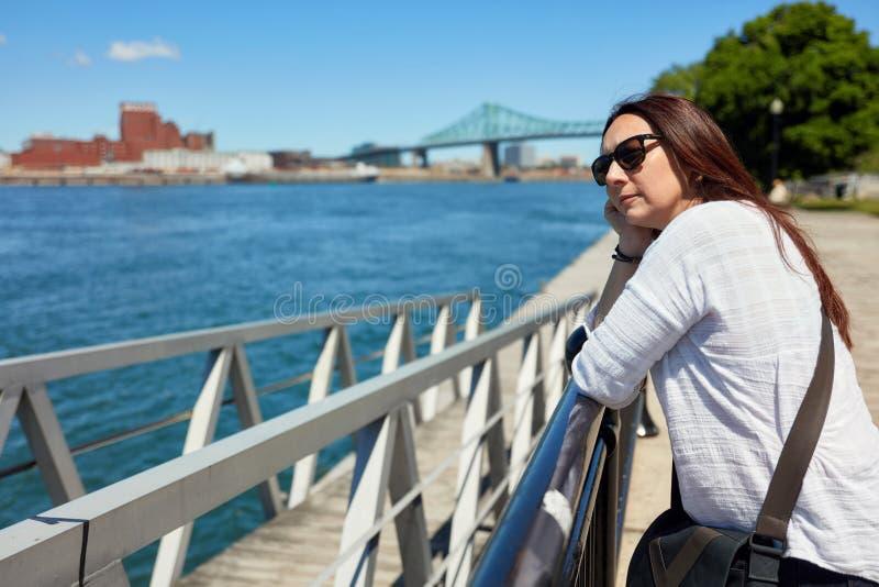 Rudzielec kobieta ogląda scenerię Montreal miasto i Świątobliwa Lawrance rzeka na pogodnym letnim dniu w Quebec, Kanada fotografia royalty free