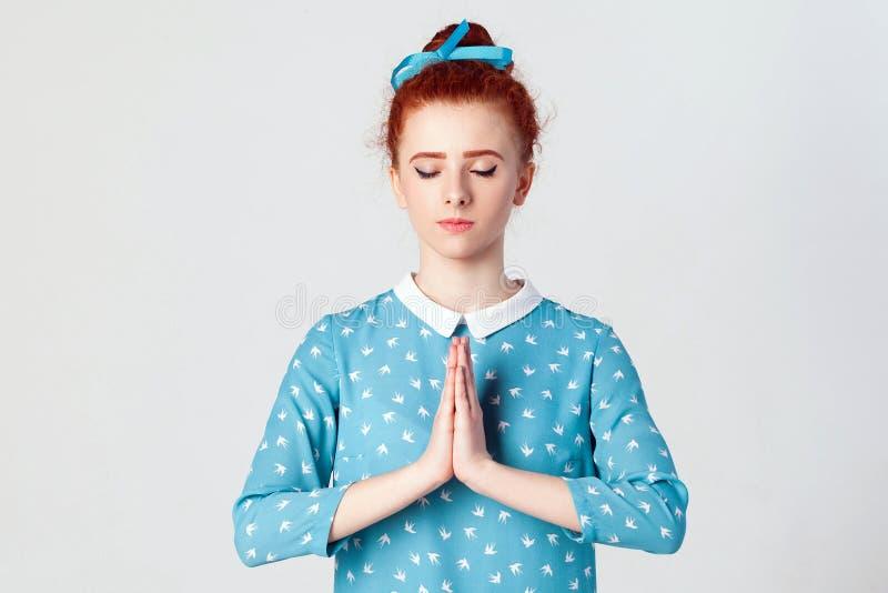 Rudzielec kobieta, trzyma ręki w namaste lub modlitwie utrzymuje oczy zamykający, podczas gdy ćwiczyć joga i medytujący w domu sa zdjęcie royalty free