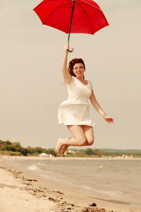 Rudzielec kobiety odprowadzenie na plażowym doskakiwaniu z parasolem obrazy stock