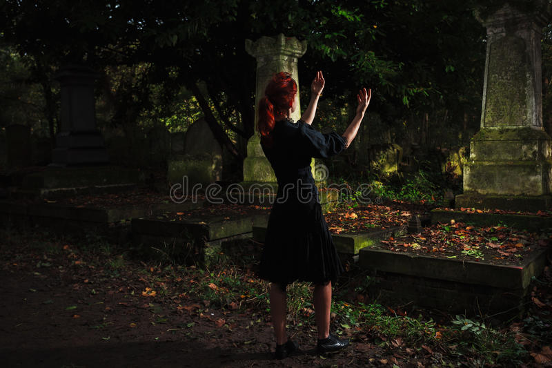 Rudzielec kobiety spełniania rytuał przy grób fotografia stock