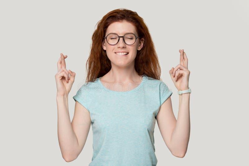 Rudzielec kobiety zamykający oczy krzyżuje palce pytają na dobre szczęście zdjęcia stock