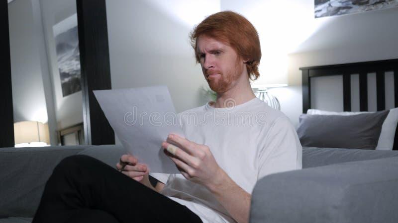 Rudzielec mężczyzna czytania list, Siedzi na kanapie zdjęcie royalty free