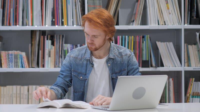 Rudzielec mężczyzna czytelnicza książka, siedzi w bibliotece obrazy royalty free