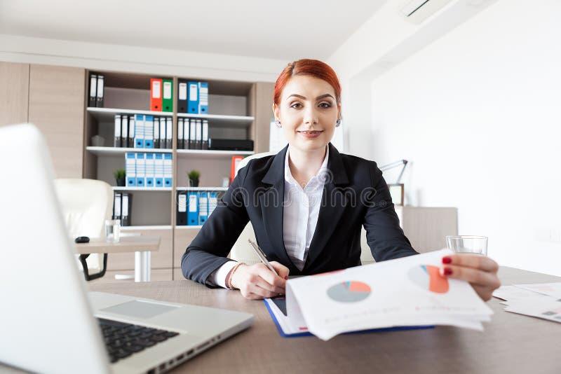 Rudzielec młody bizneswoman sprawdza dokumenty w jej biurze fotografia stock