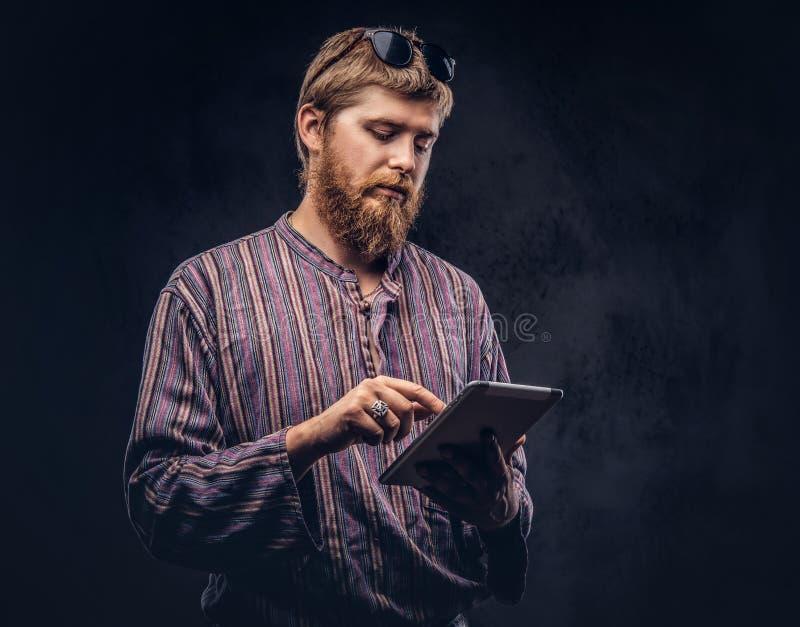 Rudzielec modnisia brodaty facet ubierał w staromodnej koszula używać pastylka komputer na ciemnym tle obraz royalty free