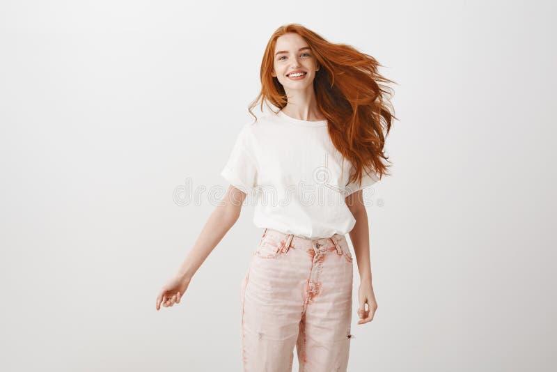 Rudzielec reguły świat Portret beztroska szczęśliwa i powabna kobieta z imbirowym włosy, skacze joyfully nad szarość zdjęcie stock