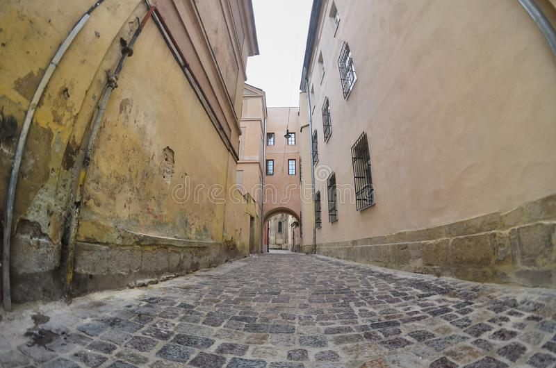 Rue étroite avec un chemin des pavés Passez entre les vieux gratte-ciel historiques à Lviv, Ukraine image libre de droits
