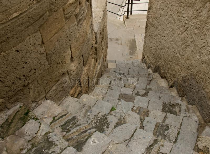 Rue étroite dans la vieille ville avec l'escalier en pierre du vieux pavé rond vers le bas images libres de droits
