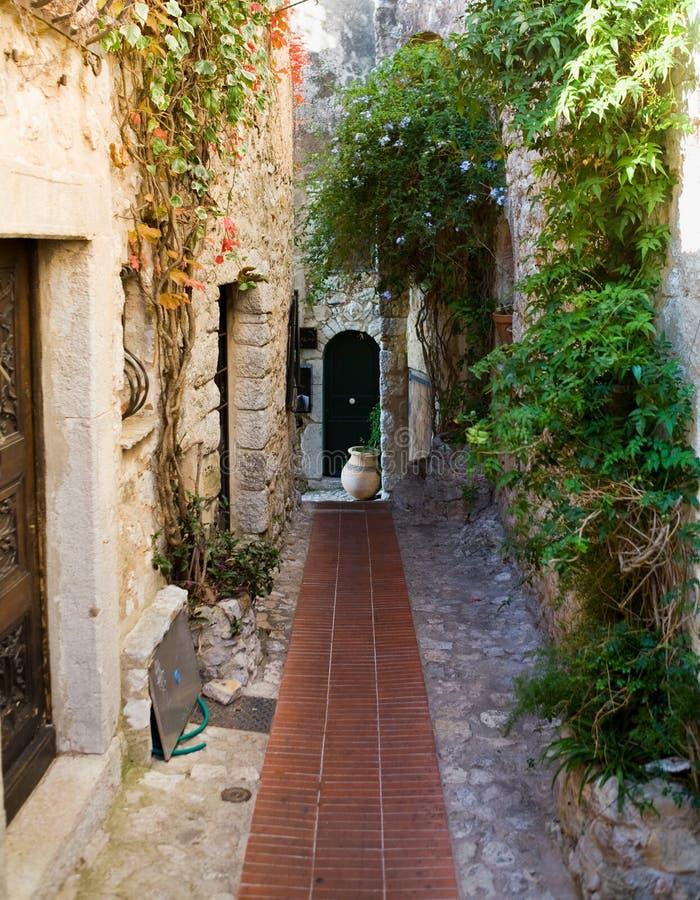 Rue étroite dans le village d'Eze avec un bac photos stock