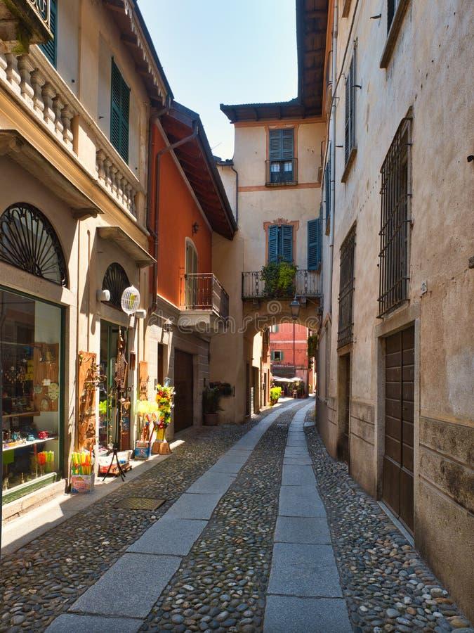 Rue étroite et pavée en cailloutis avec des magasins dans le village d'Orta San Giulio Italie un après-midi d'été photographie stock libre de droits