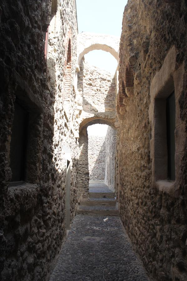 Rue étroite et pavée en cailloutis d'une petite ville en Sardaigne photos libres de droits