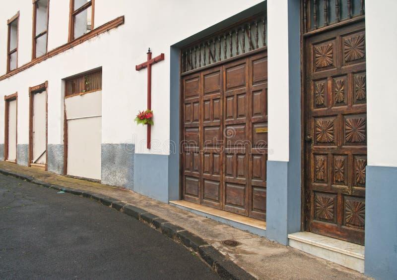 Rue avec la grande croix sur le vieux mur blanc de bâtiment images libres de droits