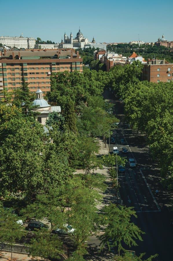 Rue avec le trafic au beau milieu des arbres et des immeubles à Madrid images stock