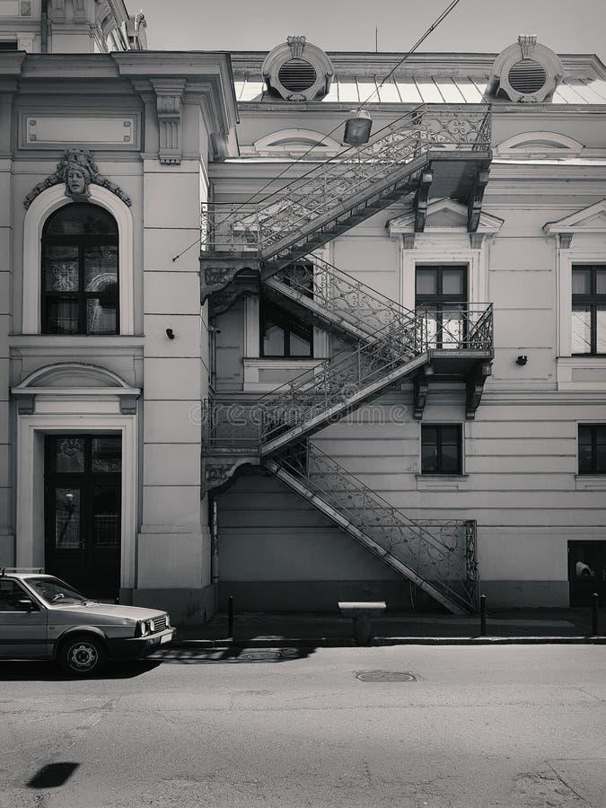 Rue avec le vieux bâtiment et une voiture, en noir et blanc image stock