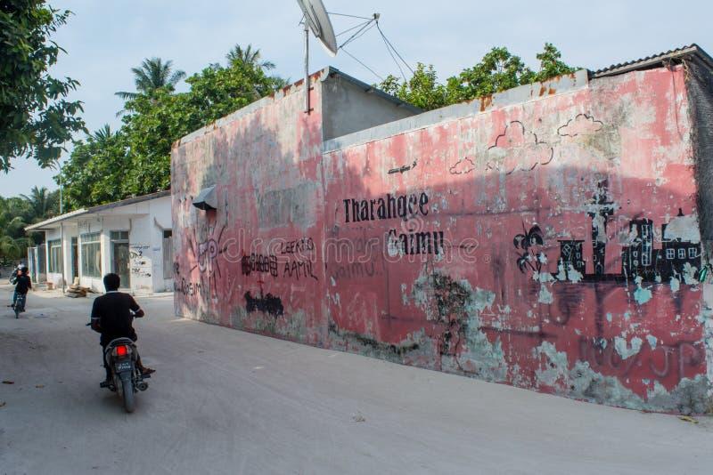 Rue avec les bâtiments, les vélos et les personnes locaux pendant le jour ensoleillé situé à l'île tropicale Maamigili images libres de droits