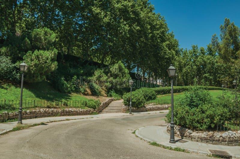Rue avec les courriers légers passant par un jardin à Madrid photos stock