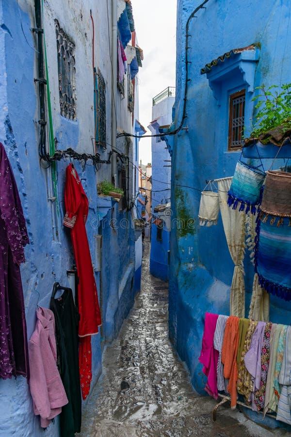 Rue bleue serrée et étroite en Médina de Chefchaouen Maroc avec l'habillement à vendre photo libre de droits