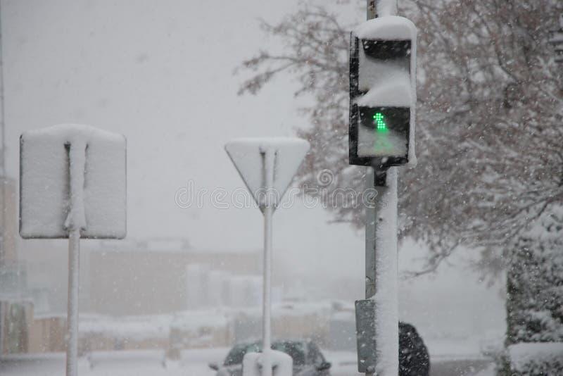 Rue couverte dans la neige par le temps brumeux lourd dans la ville de réverbère vert photographie stock libre de droits