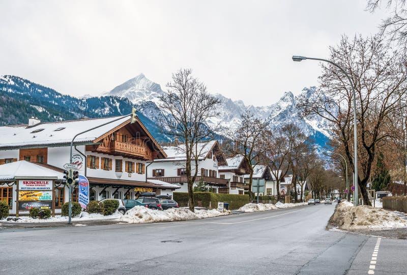 Rue d'une petites ville et station de sports d'hiver alpines avec les maisons, la route et les montagnes typiques photographie stock libre de droits