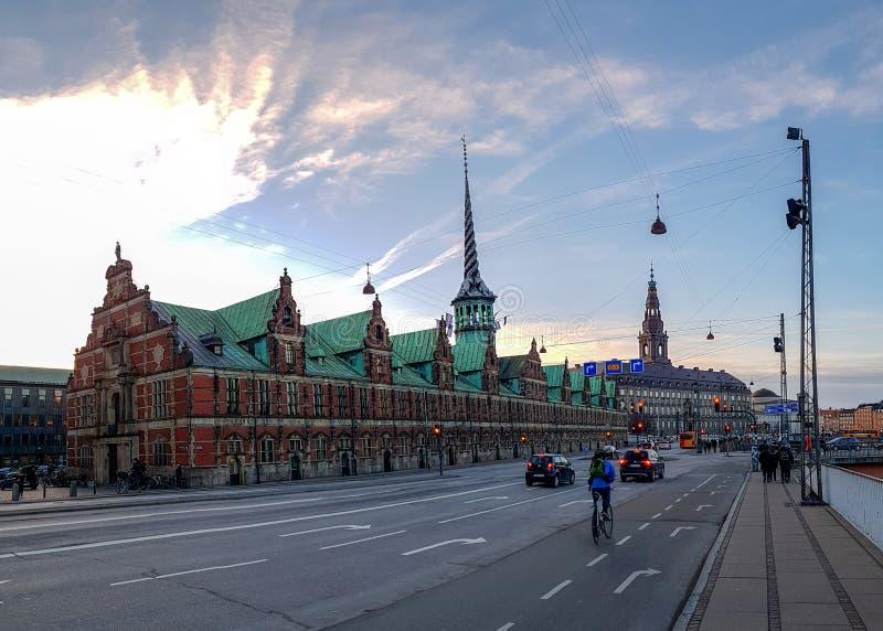 Rue de Copenhague avec la route, les cyclistes, les personnes et bâtiment Borsen de bourse des valeurs de Copenhague le vieux sur image libre de droits