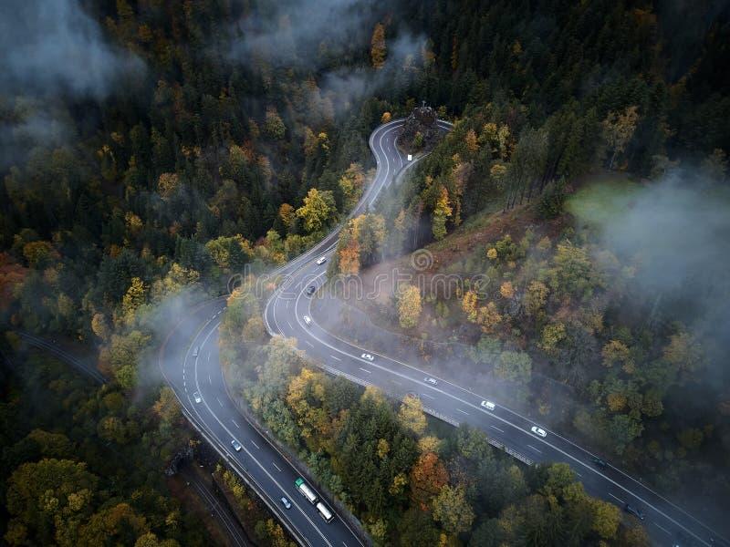 Rue de cuvette ci-dessus une forêt brumeuse à l'automne, au vol de vue aérienne par les nuages avec le brouillard et aux arbres image libre de droits
