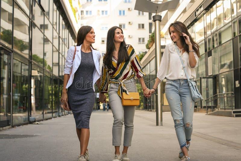 Rue de marche d'amis féminins, tenant des mains images stock