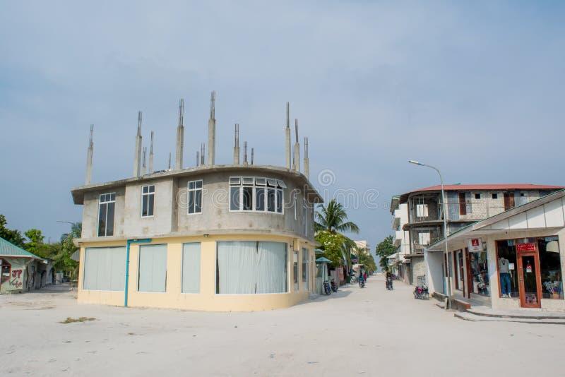 Rue de village avec les bâtiments, la route, les vélos et les personnes locaux pendant le jour ensoleillé situé à l'île tropicale photographie stock