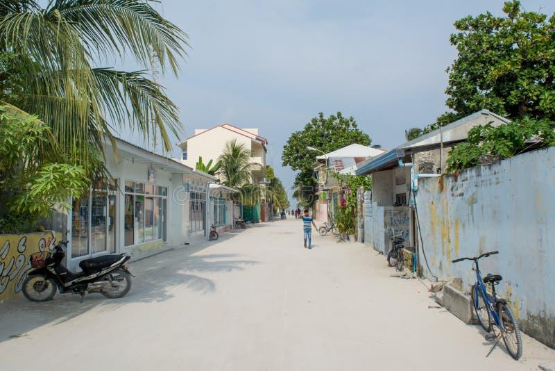 Rue de village avec les bâtiments, les vélos et les personnes locaux pendant le jour ensoleillé situé à l'île tropicale Maamigili image stock