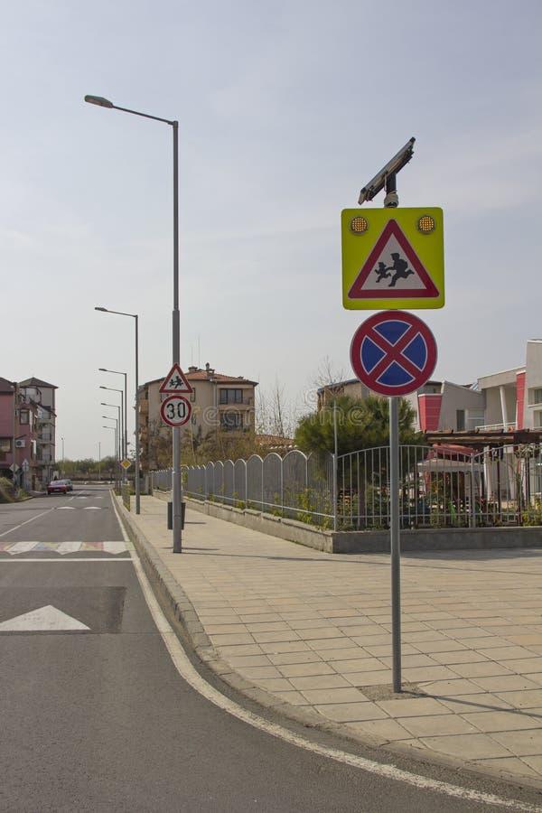 Rue de ville avec un passage pour pi?tons, une bosse de vitesse et un signe de pr?caution ?enfants ?pr?s d'un beau jardin d'enfan images stock