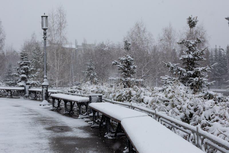 Rue de ville de neige, le parc, bancs sous la neige, il est tombé en début de l'été images libres de droits