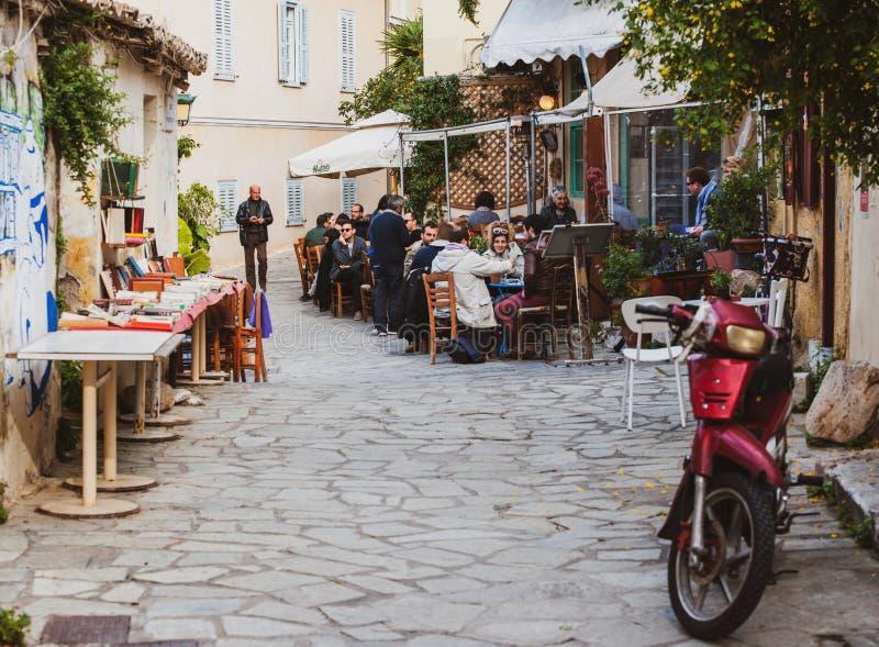 Rue grecque mignonne minuscule avec des personnes appr?ciant le restaurant de rue de nourriture image stock