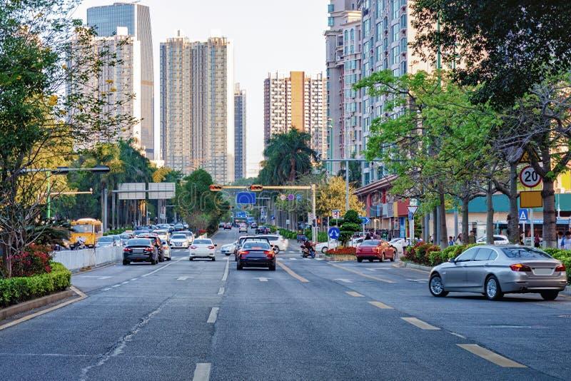 Rue occupée de ville de Shenzhen avec la voiture mobile, moto, immeuble de bureaux, gratte-ciel photos stock
