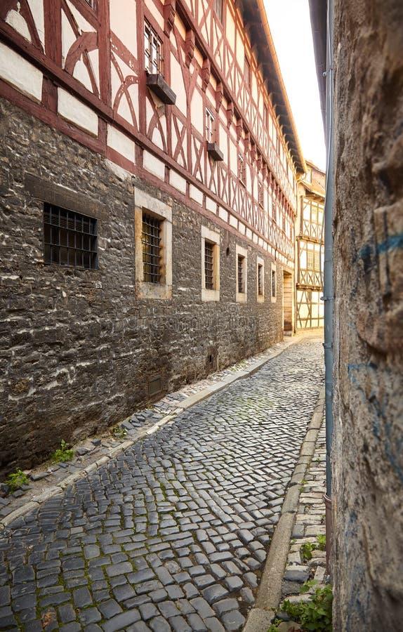 Rue pavée en cailloutis étroite entre les maisons à colombage au centre de la ville historique d'Erfurt image stock