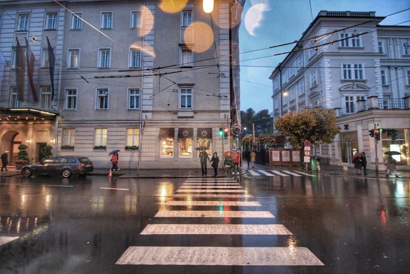 Rue pluvieuse avec les lumières et le vieux bâtiment photo stock