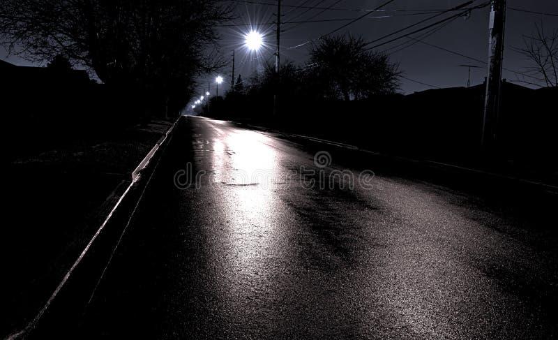 Rue pluvieuse suburbaine la nuit images stock