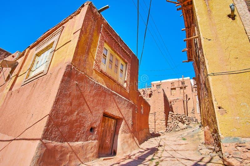 Rue raide de montée dans le village de montagne médiéval avec les maisons d'adobe rouges des deux côtés, Abyaneh, Iran photos libres de droits