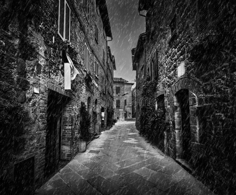 Rue sombre dans une vieille ville italienne en Toscane, Italie Pleuvoir, noir et blanc photo stock