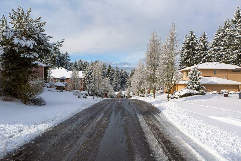 Rue suburbaine de voisinage dégivrant le jour de neige d'hiver photo stock